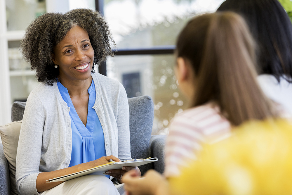 Teenage girl and mother talk with a friendly counselor in her office.